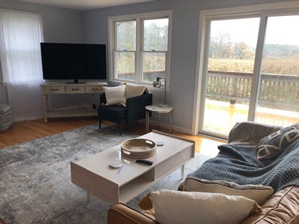 Eastham Cape Cod vacation rental - Living area with fireplace, TV and access to the deck.