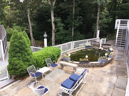 Cotuit- near Loop Beach Cape Cod vacation rental - Slate patio with koi pond and fire pit, middle deck