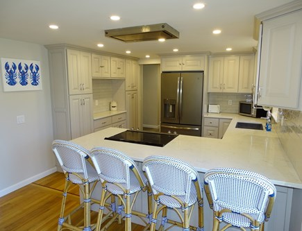 Harwich Cape Cod vacation rental - Kitchen with breakfast bar, hallway to laundry