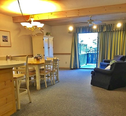 Mashpee Cape Cod vacation rental - Kitchen, dining area, & living room with sliders to the back deck