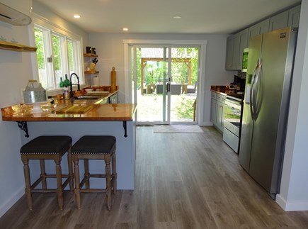 Brewster Cape Cod vacation rental - Kitchen area with breakfast bar and slider to back yard