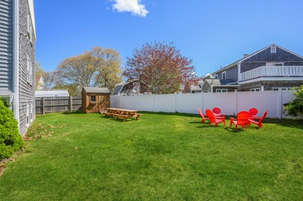 Dennis Port Cape Cod vacation rental - Back yard with sitting area, picnic tables, & charcoal grills