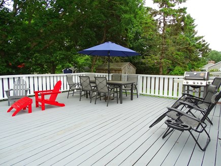 South Yarmouth Cape Cod vacation rental - Deck area with dining table, Adirondack chairs, gas grill