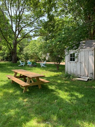 Brewster Cape Cod vacation rental - Backyard with shed, picnic table, fire pit, and Adirondacks