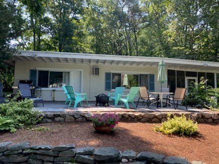 Falmouth, Sippewisset Cape Cod vacation rental - Exterior, fire pit and dining table.  Weber gas grill.