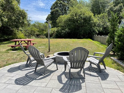 Eastham Cape Cod vacation rental - Level backyard for lawn games and patio with fire pit for s'mores