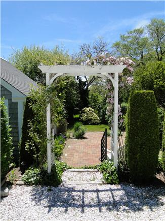 Chatham Cape Cod vacation rental - Arbor entrance to patio surrounded by lush gardens and play areas