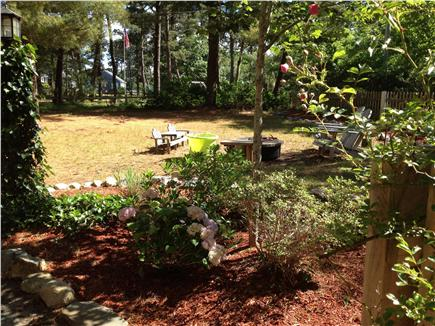 Dennis Port Cape Cod vacation rental - Firepit and adirondack chairs in front yard