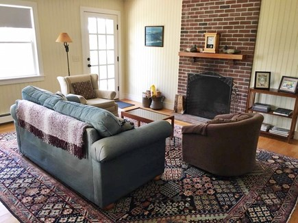 Eastham Cape Cod vacation rental - Living area with fireplace and door onto deck
