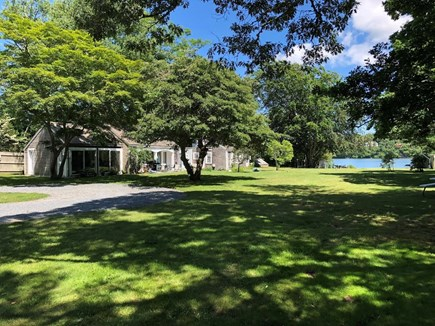 Dennis, Scargo Lake Cape Cod vacation rental - House and lawn leading to lakefront with boathouse and firepit.