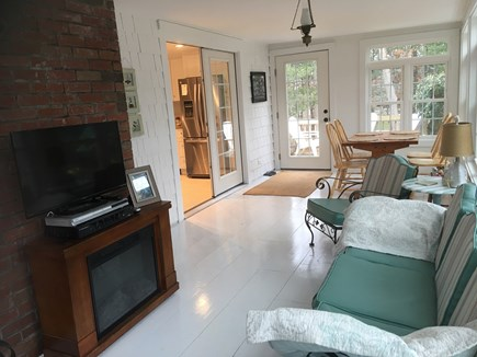 Dennis Cape Cod vacation rental - Sunroom with electric fireplace and TV opens to kitchen and deck