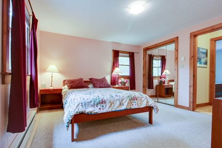 Edgartown Martha's Vineyard vacation rental - A queen bed under a printed coverlet, modern wood furniture